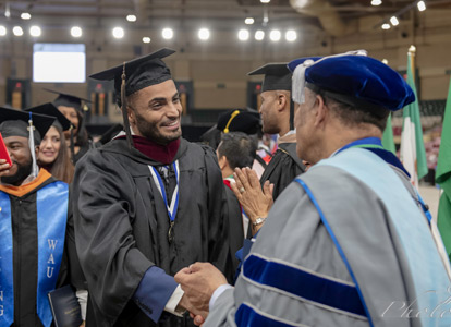 President shaking hands with graduating student