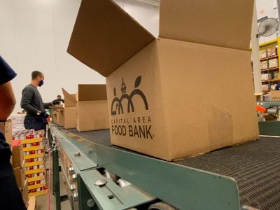 Capital Food Bank Box on the conveyor belt.